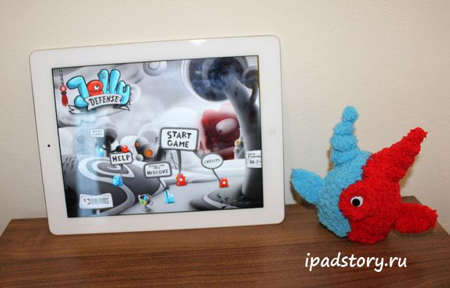 вязаный персонаж Jelly Defense рядом с iPad